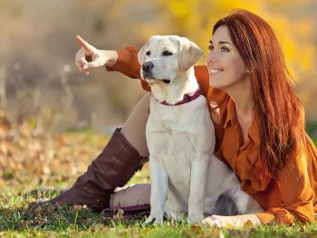 young woman teaching her labrador